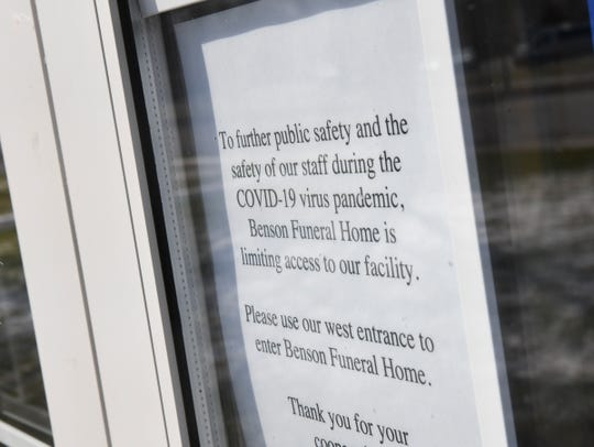 A sign announces policies to visitors at Benson Funeral Home & Cremation Service Thursday, April 9, 2020, in St. Cloud.