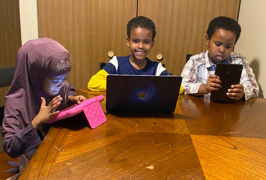 Hafso, Mustafa and Mohamed Mohamud work on assignments from their St. Joseph home.