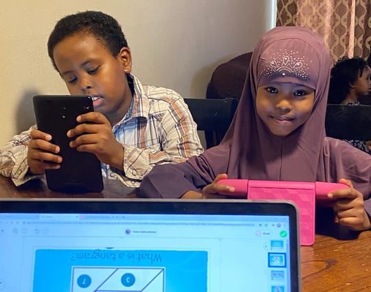 Kennedy Community School students Mohamed and Hafso Mohamud work on assignments at home in St. Joseph.