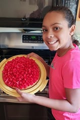 Keira Alexander, a sixth-grader at North Junior High in St. Cloud, shows the cake she baked from scratch on March 30, 2020 — the first day of distance learning — when she couldn't access her schoolwork because the Schoology website had crashed.