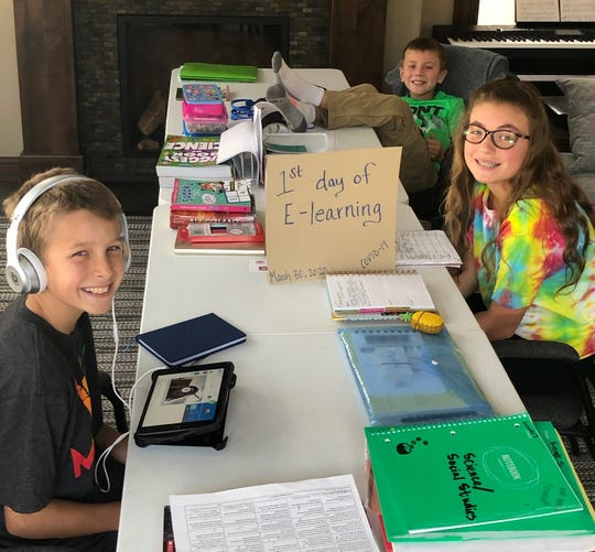 St. Cloud school district students Everett, Cohen and Addison Stine set up shop March 30, 2020 on the first day of distance learning.
