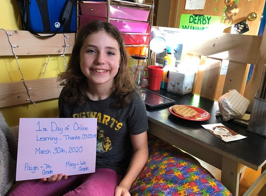 Macy Roche, a sixth-grader at South Junior High in St. Cloud, holds a sign marking the first day of distance learning on March 30, 2020.