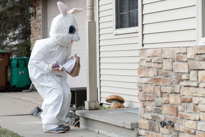 Evan Heise, 14, hops as he delivers meals dressed as the Easter Bunny on Thursday in Stevens Point. Heise, along with his mother, Serena Sblendorio, deliver meals each week day to families in the Bannach School neighborhood.