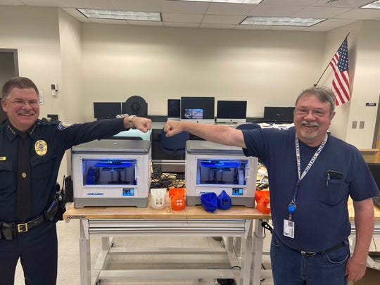 Tallahassee Community College Police Chief Greg Gibson, left, and Mike Vickers, manager of the Computer Technology building, pictured with a display of 3-D printable protective masks.