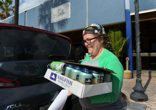 "Taylor Welchel, brand manager at Sailfish Brewing Company, prepares to deliver an order of beer, two 6-packs and two 4-packs, to a customer in Vero Beach on Wednesday, April 8, 2020, from their brewery in downtown Fort Pierce. Sailfish is offering beer delivery in parts of Indian River and St. Lucie counties to keep their business going during the COVID-19 pandemic. ""To reach the people,"" Welchel said. Sailfish offers delivery service for a $5 fee, and a $40 minimum purchase."