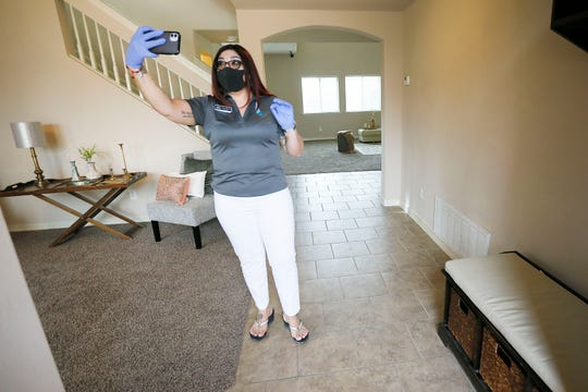 Realtor Laura Spears takes a video of a home with her phone for a prospective buyer Thursday, April 9, in El Paso. Spears records videos with her own commentary and then sends them to the perspective buyer via YouTube link to maintain social distancing in response to COVID-19 while still being able to show the home they are interested in.