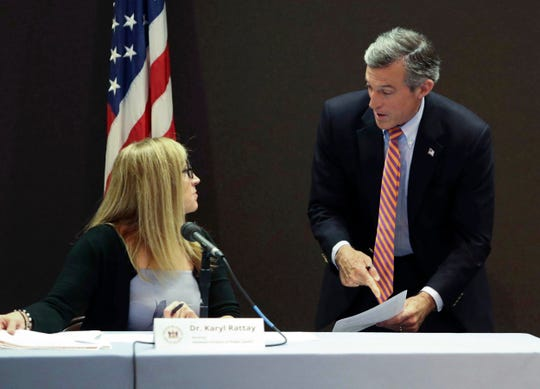 Gov. John Carney speaks with Dr. Karyl Rattay, director of the state Division of Public Health, before administration offices conduct a press briefing on the state's response to Covid-19 Thursday at the Carvel State Building.