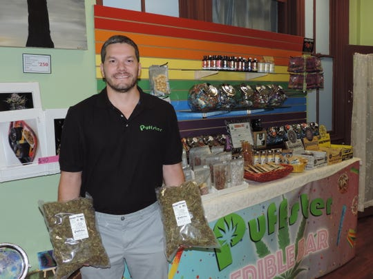 Sam Chick, co-owner of Puffster in Dover, holds bags of hemp flowers in front of displays of edible hemp and CBD products. BEN MACE/Dover Post