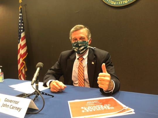 Gov. John Carney shows off his homemade mask after his press briefing Thursday, a day after the state recommended Delawareans wear cloth face coverings in public settings where social distancing is difficult to maintain. Those settings include grocery stores and pharmacies.