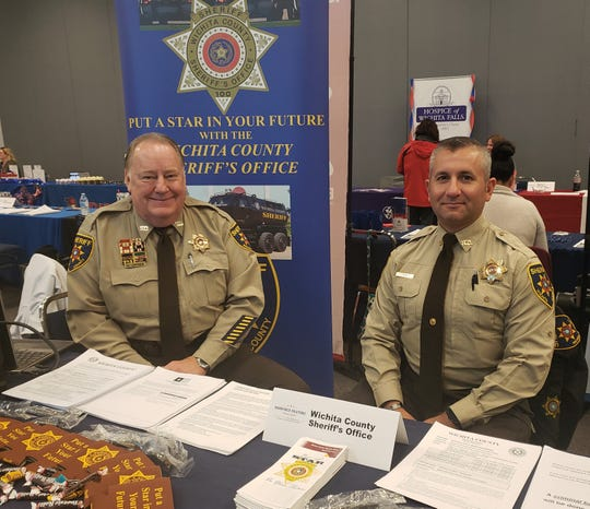 Wichita County sheriff's office deputies Melvin Joyner, left, and Brien Conner, right, recruit at a recent Workforce Solutions North Texas job fair. They are members of the Wichita County Sheriff's Office Community Services Unit.