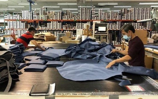 Trung Nguyen and Huy Nguyen work on making gowns at Wichita Falls Covercraft Industries. The plant has switched to producing personal protective equipment during the pandemic.