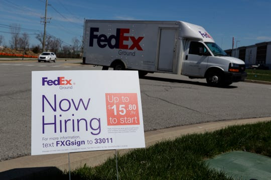 A sign advertising for jobs sits along the roadside outside a FedEx location in Zionsville, Ind., on April 2, 2020.