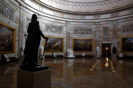A statue of President George Washington looks over an empty Capitol Rotunda on Capitol Hill in Washington, Thursday, April 9, 2020. The Capitol remains closed to visitors, and the District of Columbia is under a stay-home order for all residents in an effort to slow the spread of the coronavirus.