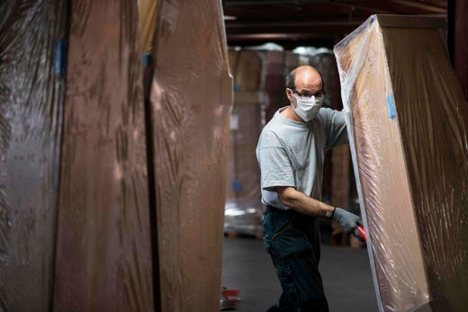 An employee of France's biggest coffin-maker, OGF group pushes a coffin in a storage room in Jussey, eastern France, on April 8, 2020, amid the spread of the COVID-19, the disease caused by the novel coronavirus.