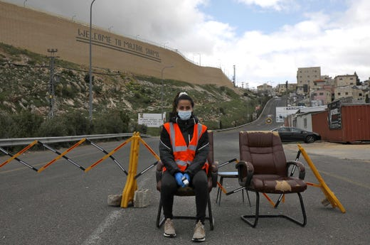 A woman stands next to a makeshift checkpoint, part of a community safety initiative in the Druze village of Majdal Shams in the Israel-annexed Golan Heights on April 9, 2020, amid the novel coronavirus epidemic.
