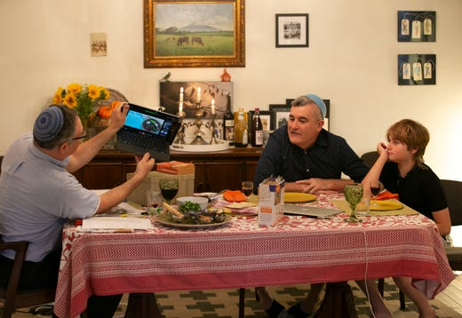 Rabbi Dean Shapiro (left) of Temple Emanuel in Tempe, angles his laptop so others online can see their Seder plate as Shapiro's partner, Haim Ainsworth and their son, Jacob Shapiro-Ainsworth, 11, look on, as they participate in an online Seder during the first night of the Jewish holiday of Passover at their home in Tempe on April 8, 2020. The Seder which included members from Temple Emanuel was being held online because of the coronavirus pandemic.