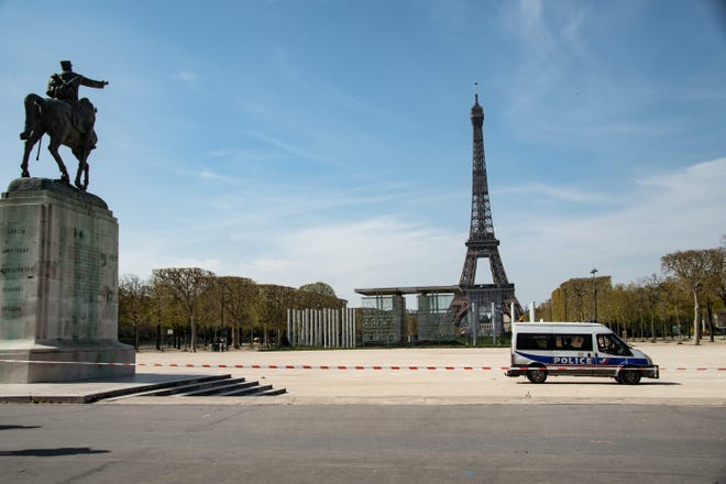 A police van is parked in the closed Jardin du Champs de Mars garden in front of the Eiffel tower in Paris on April 7, 2020, the 22nd day of a lockdown in France aimed at curbing the spread of the COVID-19 pandemic, caused by the novel coronavirus.
