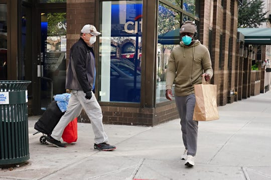Men wearing protective masks and practicing social distancing on April 08, 2020 in New York City.