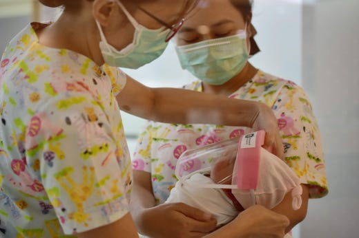 This photo taken through a glass window at a maternity ward shows nurses putting a face shield on a newborn baby, in an effort to halt the spread of the COVID-19 coronavirus, at Praram 9 Hospital in Bangkok on April 9, 2020.