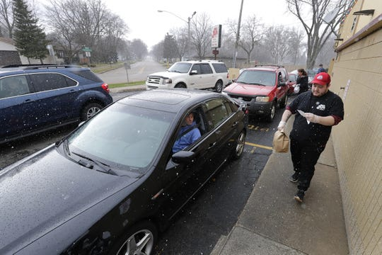 Angel Reyes delivers a drive up lunch order to Dave McCracken at JD's Drive-In on Thursday in Appleton in the midst of snow flurries. Vehicles were lined up around the entire restaurant waiting to order.