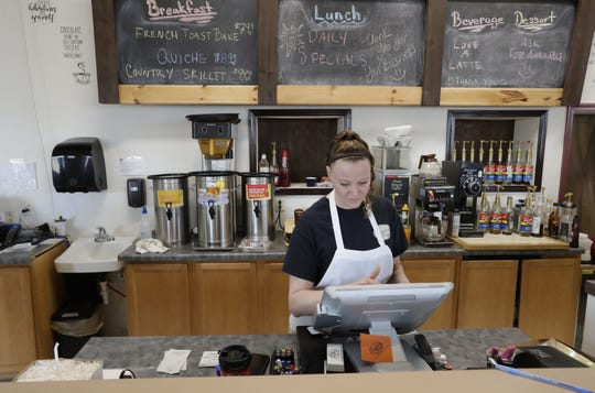 Owner Amanda Thompson rings up an order Friday at My Boondocks Cafe in Menasha.