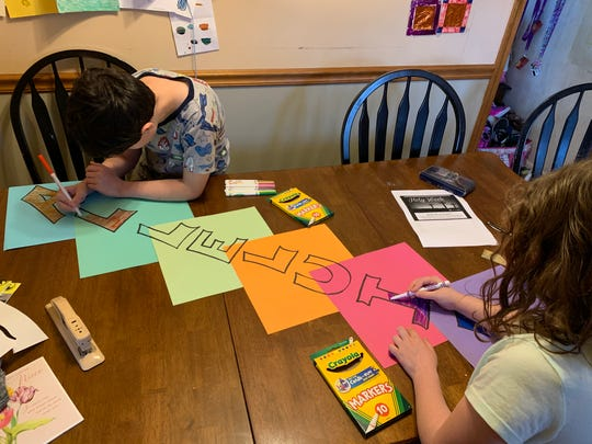 """Carmelo an Miriam Carino color an """"Alleluia"""" sign for the front door."""