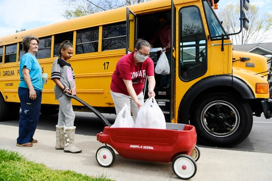 """Tabitha Banks, Montford Star Academy's cafeteria manager, places lunches into 9-year-old Abbi Franklin's wagon April 8, 2020. """"We appreciate everything they do,"""" said Franklin's grandmother, Cindy Crawford."""