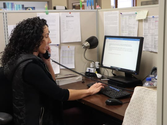 Kayla Grippe, a social worker at the Neighborhood Center's MCAT program, speaks on the phone in February at the program's headquarters. Staff now work from home and handle all cases over the phone or video chat.