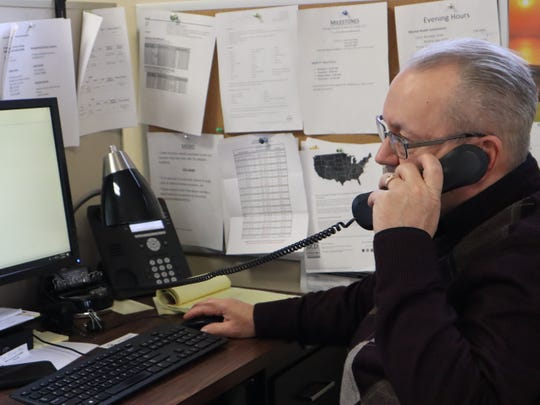 Mark Lundquist, a social worker at the Neighborhood Center's MCAT program, speaks on the phone in February at the program's headquarters. He currently works from home.