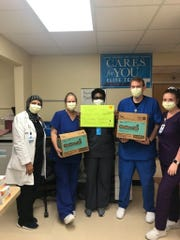 Workers at  Steward Health Care System's Rockledge Medical Center accept a donation of Girl Scout Cookies.