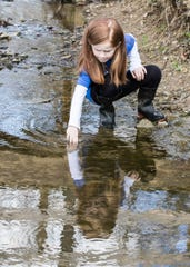 "Alexis Jones turns over rocks in a creek at Earthworks Junction as she looks for potential animals to turn into the STEM ""Wild Eyes"" program."