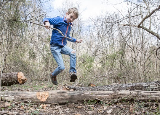 Wiley Lewis excitedly jumps over a log at Buzzard's Roost after finding tadpoles to post for the Wild Eyes project on April 2, 2020.