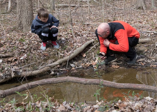 Miles Rathkamp and his father Keegan take pictures of animals in a creek at Buzzard's Roost as part of the Wild Eyes program through STEM at Chillicothe City Schools.