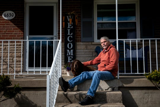 Chris Hahn, 63, sits on his porch with his Labrador Retriever, Lucy, in Green Township on Thursday, April 9, 2020. Hahn tested positive for COVID-19 at the end of the March. He spent three and a half days in the hospital. His two brothers also tested positive, including his older brother, Gary, who passed away on April 5.