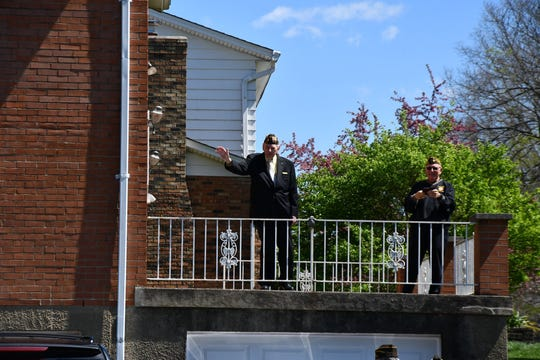 Edward Burke waves from a porch to a gathering of well-wishers Thursday, April 9, 2020, outside his Green Township residence.