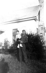 In this image provided by the McConnell Center at the University of Louisville, Mitch McConnell is held by his father Addison Mitchell McConnell in front of a relative's house in Five Points, Ala, in 1944, shortly before he was stricken with polio. McConnell would regularly travel just over 50 miles to Warm Springs, Ga., for treatment. His dad was home on leave from basic training at Fort Bliss, Texas. As the coronavirus pandemic unfolds, Senate Majority Leader Mitch McConnell flashes back to an earlier crisis that gripped the nation, and his own life, when he was a boy. He was struck with polio. (McConnell Center at the University of Louisville via AP)