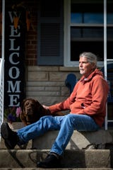 Chris Hahn, 63, sits on his porch with his Labrador Retriever, Lucy, in Green Township on Thursday, April 9, 2020. Hahn tested positive for COVID-19 at the end of the March.