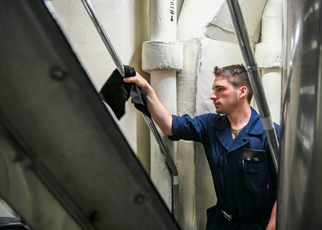 Operations Specialist Seaman Logan Quirk, from Bellevue, Kentucky, cleans and sanitizes a handrail aboard the Ticonderoga-class guided-missile cruiser USS Normandy (CG 60).