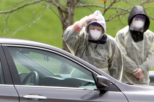 Paperwork is checked for people in a car as the arrive at Middlesex County's COVID-19 testing facility at the State Motor Vehicle Commission on Rt. 130 in South Brunswick Friday, April 10, 2020.