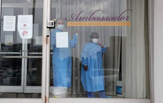 Workers watch as Rev W.J. Rideout and the SEIU Michigan Healthcare union protest working conditions at the Ambassador nursing home on April 9, 2020, in Detroit. Workers at the home were just recently given the necessary PPE needed to treat patients.
