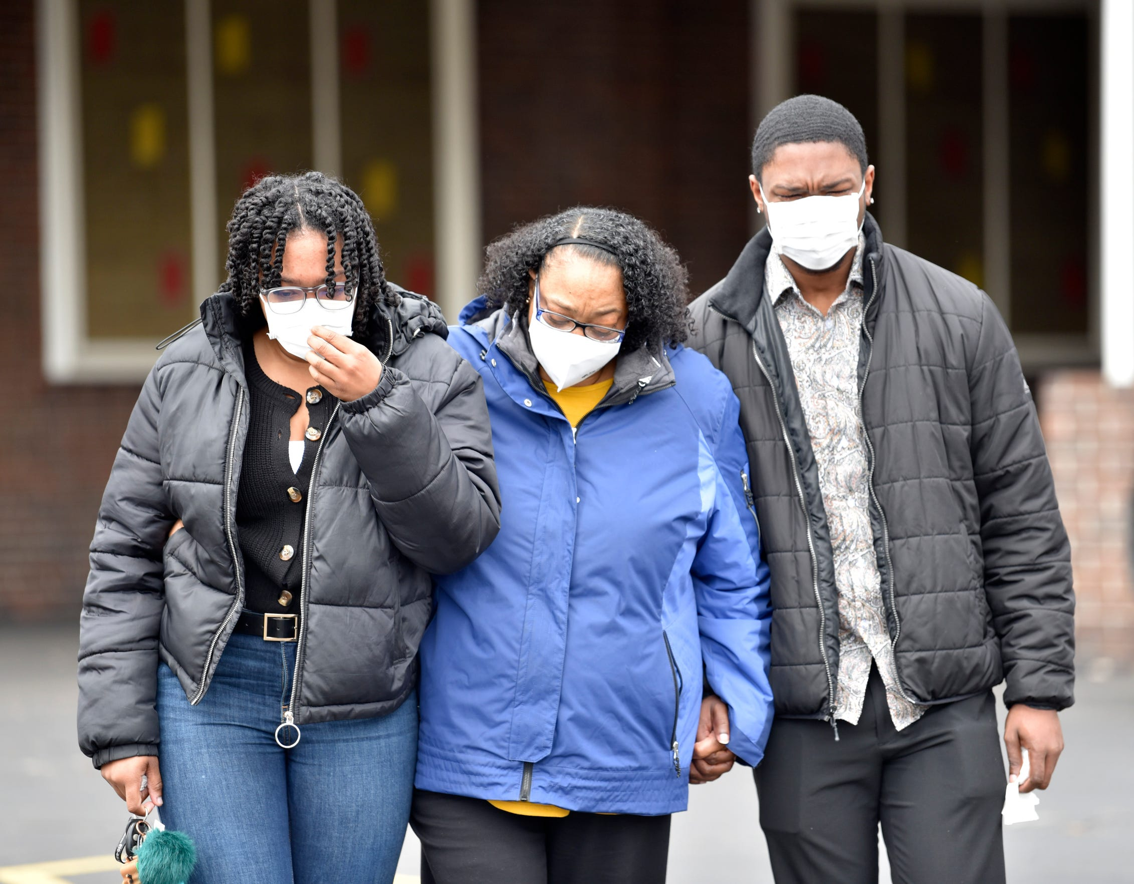 Tonya Brown, center, and her children Rochelle Pompey and Ronnie Pompey Jr., all of Flint, cry as they leave the funeral home. Brown is Freddie Lee Brown Jr.'s sister.