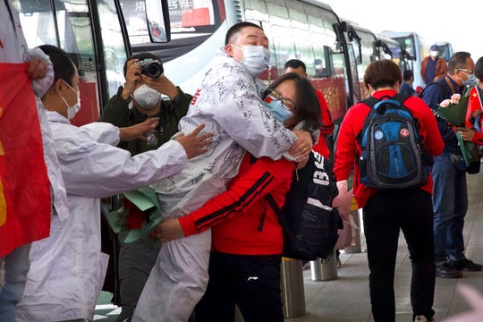 A medical worker from China's Jilin Province, in red, embraces a colleague from Wuhan as she prepares to return home at Wuhan Tianhe International Airport in Wuhan in central China's Hubei Province. Within hours of China lifting an 11-week lockdown on the central city of Wuhan early Wednesday, tens of thousands people had left the city by train and plane alone, according to local media reports.