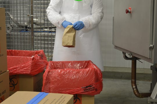 A worker prepares to place a dirty N95 mask into the spiral oven for decontamination.