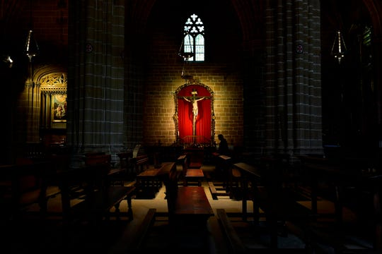 A priest walks by a figure depicting the crucifixion of Jesus Christ, center back, in an empty Santa Maria Cathedral during Good Friday after celebrations and ceremonies were cancelled due to the outbreak of coronavirus, in Pamplona, northern Spain, Friday.