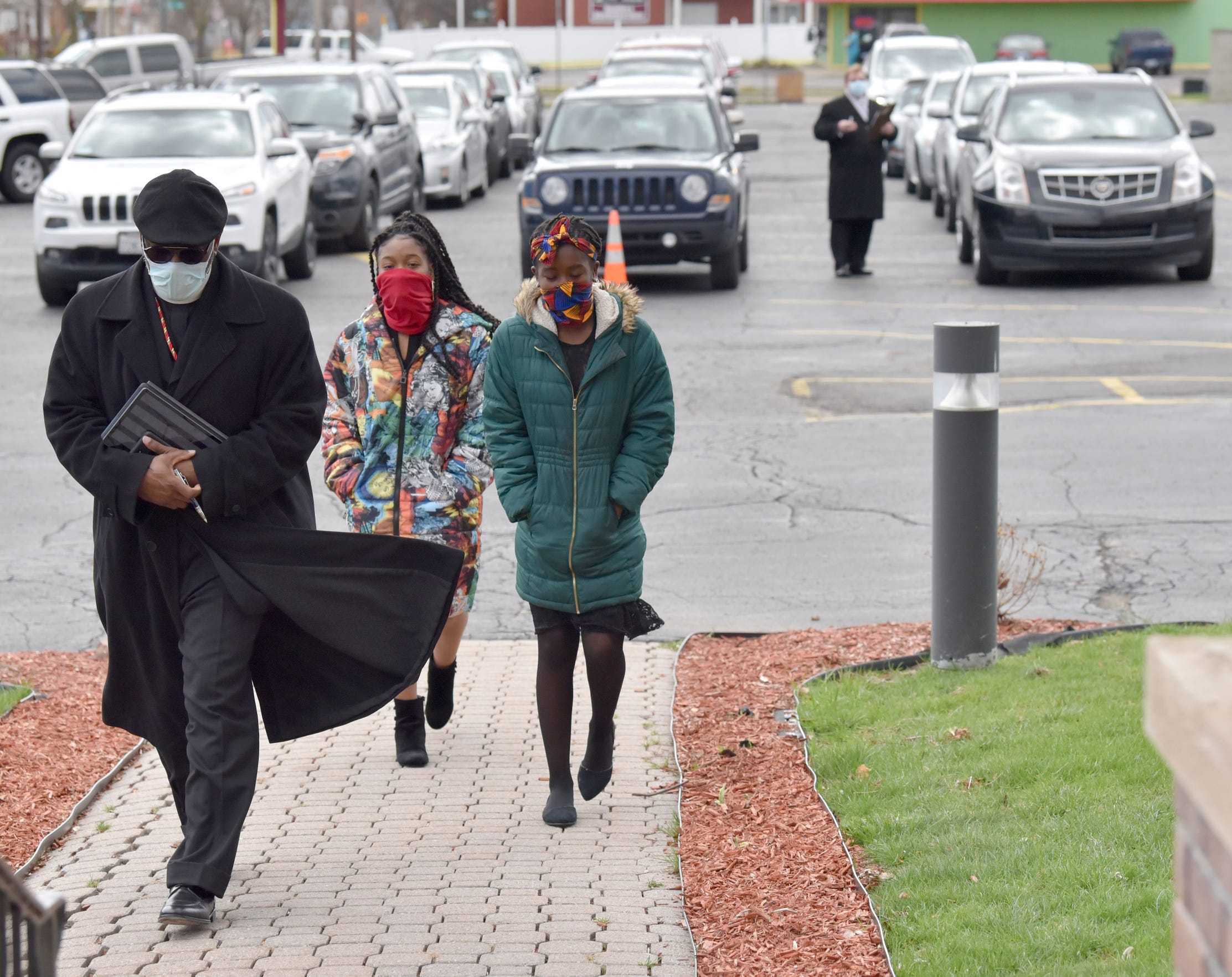 Jackson Memorial Temple Church of God in Christ Pastor Kiemba Knowlin and his daughters Nehderi Knowlin, center, and Zhenya Knowlin, all of New Baltimore, enter the funeral home to pay respects as other invited guests wait in their cars for their turn.