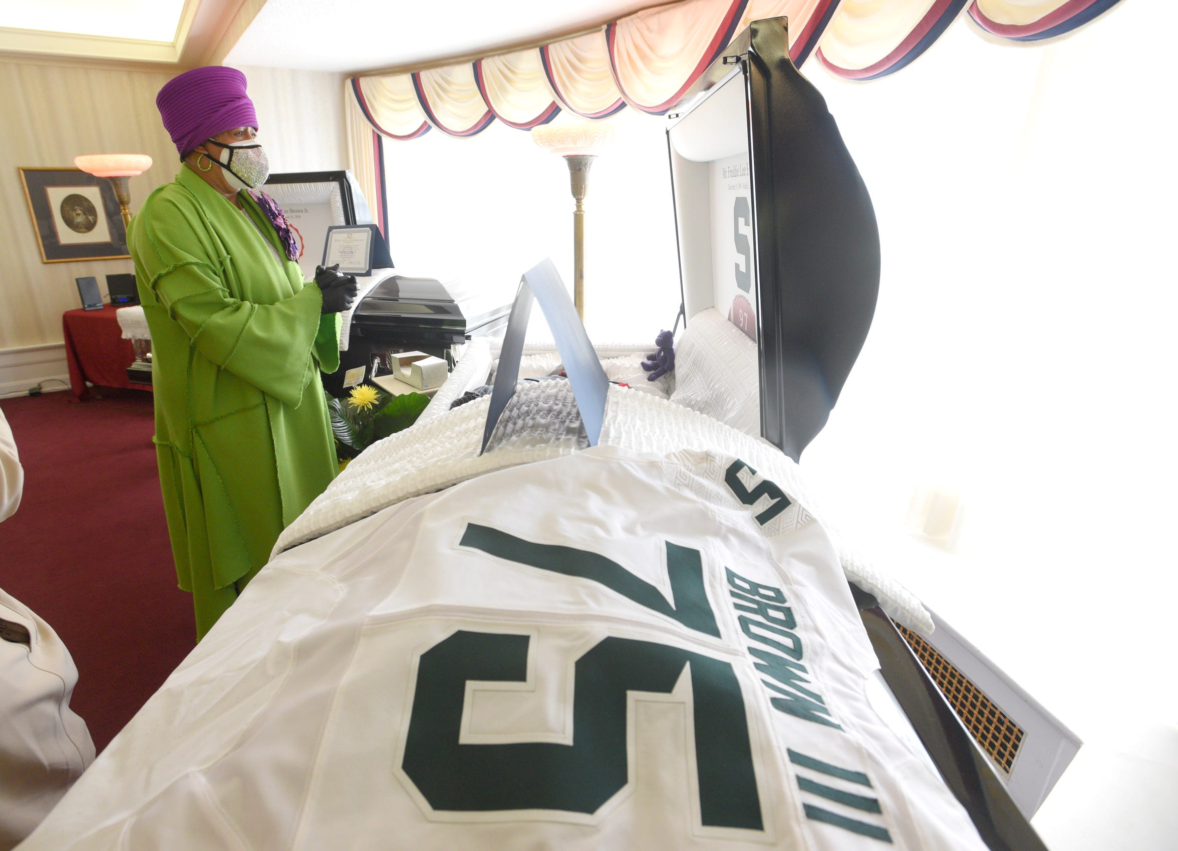 Sandy Brown cries as she pays respects to her son, Freddie Lee Brown III, who dreamed of playing football at Michigan State this fall as a walk-on.