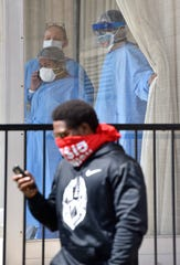 People inside the Ambassador Nursing and Rehabilitation Center wear PPE as they watch a protest in front of the Ambassador Nursing and Rehabilitation Center on E. Jefferson in Detroit on Thursday, April 9, 2020.