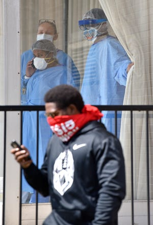 People inside the Ambassador Nursing and Rehabilitation Center wear PPEs as they watch a protest in front of the Ambassador Nursing and Rehabilitation Center on E. Jefferson in Detroit, Thursday afternoon, April 9, 2020.