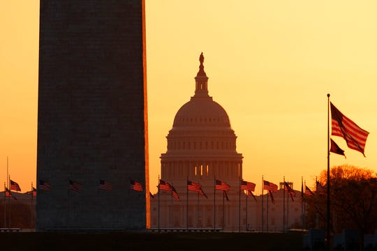 In this March 18, 2020, file photo, the Washington Monument and the U.S. Capitol are seen in Washington, at sunrise.