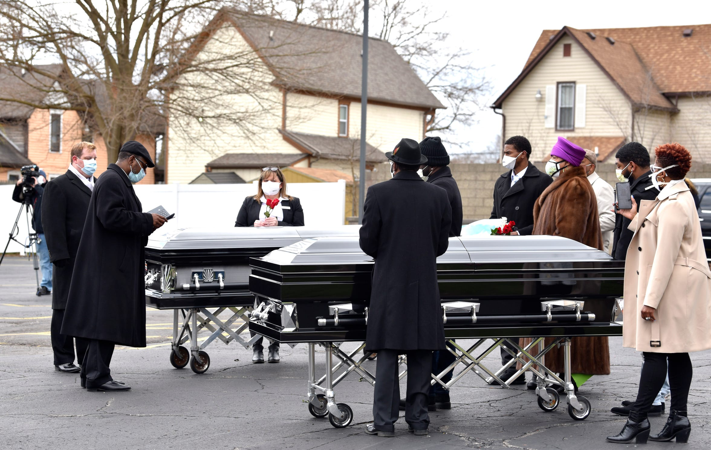 Jackson Memorial Temple Church of God in Christ Pastor Kiemba Knowlin, second from left, conducts the graveside service in the funeral home parking lot instead of the cemetery, due to COVID-19.